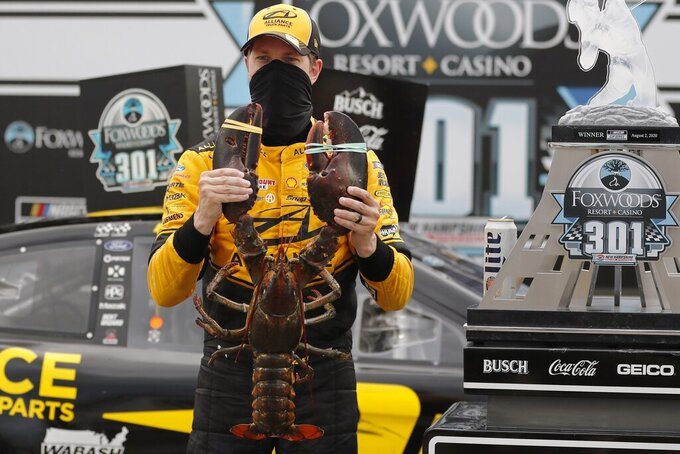 Driver Brad Keselowski holds a giant lobster to celebrate his victory in a NASCAR Cup Series auto race, Sunday, Aug. 2, 2020, at the New Hampshire Motor Speedway in Loudon, N.H. (AP Photo/Charles Krupa)