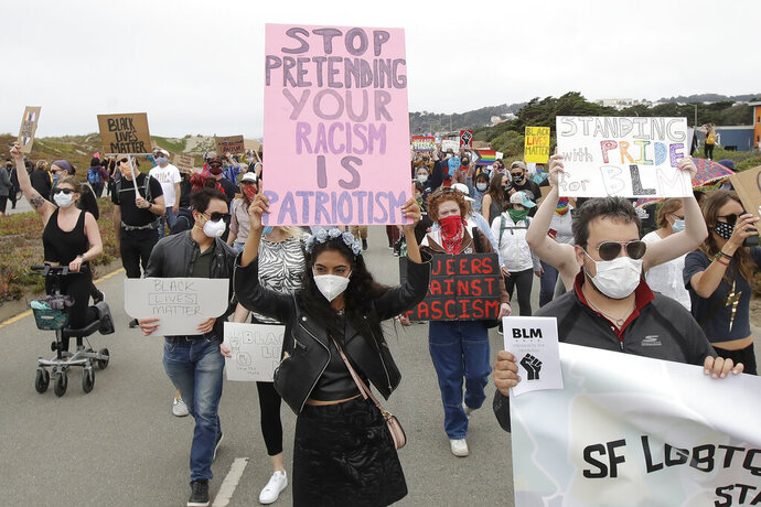 Sarzana Khan, center, and Gabriel Reyla, right, march with gay activists and suppoters on the Great Highway at Ocean Beach in San Francisco, Sunday, June 14, 2020, at a protest over the Memorial Day death of George Floyd, who died after being restrained by Minneapolis police. (AP Photo/Jeff Chiu)