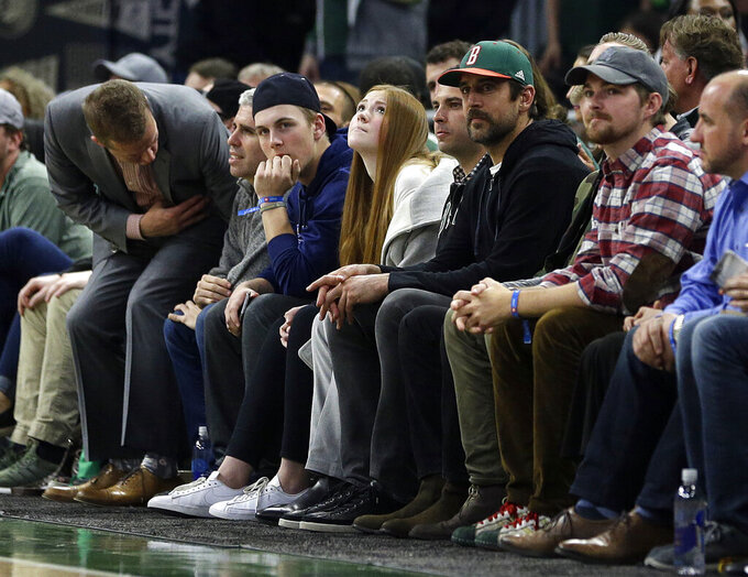 Green Bay Packers quarterback Aaron Rodgers, with green cap, watches during the second half of an NBA basketball game between the Milwaukee Bucks and the Oklahoma City Thunder Wednesday, April 10, 2019, in Milwaukee. (AP Photo/Aaron Gash)
