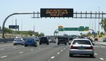 The Arizona Department of Transportation posts new signage along highways urging the public to wear face coverings due to the recent surge in coronavirus cases Sunday, June 21, 2020, in Phoenix. (AP Photo/Ross D. Franklin)
