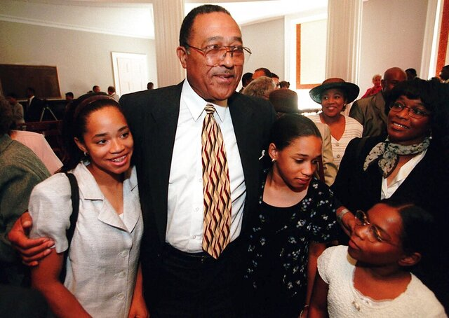 "FILE - In this Aug. 2, 1999 file photo, N.C. Supreme Court Justice Henry Frye gets hugs from his granddaughters Whitney Frye, 13, left, Jordan Frye, 11, middle, and Endya,10 in Raleigh, N.C.  In North Carolina's Supreme Court chamber hangs a towering painting of Chief Justice Thomas Ruffin, a 19th century slave owner and jurist who authored a notorious opinion about the ""absolute"" rights of slaveholders over the enslaved. Two African American chief justices have sat on the bench beneath Ruffin's stare: Frye who served as chief justice for about a year from 1999 to 2000 after 16 years as an associate justice; and Cheri Beasley, who was an associate justice for about seven years before she was appointed as chief justice in 2019.   (Scott Sharpe/The News & Observer via AP)"