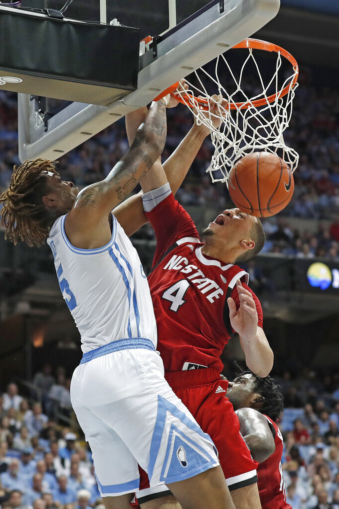 North Carolina forward Armando Bacot (5) dunks over North Carolina State forward Jericole Hellems (4) during the first half of an NCAA college basketball game in Chapel Hill, N.C., Tuesday, Feb. 25, 2020. (AP Photo/Gerry Broome)