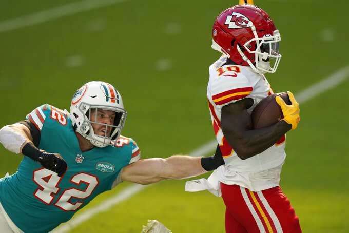 Kansas City Chiefs wide receiver Tyreek Hill (10) scores a touchdown as Miami Dolphins defensive back Clayton Fejedelem (42) attempt to tackle, during the first half of an NFL football game, Sunday, Dec. 13, 2020, in Miami Gardens, Fla. (AP Photo/Lynne Sladky)