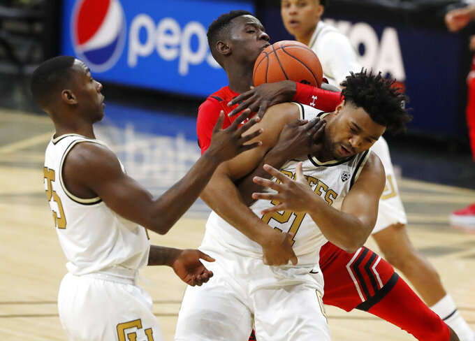 Utah center Lahat Thioune, back, wrestles away a rebound from Colorado forward Evan Battey, front right, as Colorado guard McKinley Wright IV, left, looks on in the first half of an NCAA college basketball game Sunday, Jan. 12, 2020, in Boulder, Colo. (AP Photo/David Zalubowski)
