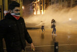 Anti-government protesters are sprayed by a water canon, during ongoing protests against the political elites who have ruled the country for decades, in Beirut, Lebanon, Sunday, Jan. 19, 2020. Lebanese security forces used tear gas, water cannons and rubber bullets in clashes with hundreds of anti-government protesters outside the country's Parliament on Sunday, as violence continued to escalate in a week of rioting in the capital. (AP Photo/Hassan Ammar)