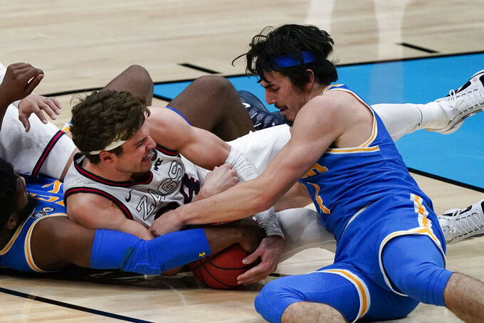 Gonzaga forward Corey Kispert (24) and UCLA guard Jaime Jaquez Jr., right, battle for a loose ball during the second half of a men's Final Four NCAA college basketball tournament semifinal game, Saturday, April 3, 2021, at Lucas Oil Stadium in Indianapolis. (AP Photo/Michael Conroy)