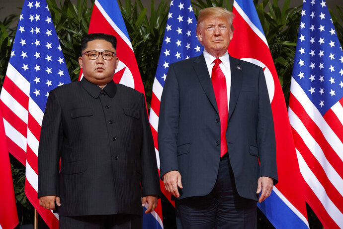 FILE - In this June 12, 2018, file photo, U.S. President Donald Trump, right, meets with North Korean leader Kim Jong Un on Sentosa Island, in Singapore. The U.S. strike that killed Iran's top military commander may have had an indirect casualty: a diplomatic solution to denuclearizing North Korea. Experts say the escalation of tensions between Washington and Tehran will diminish already fading hopes for such an outcome and inspire North Korea's decision-makers to tighten their hold on the weapons they see, perhaps correctly, as their strongest guarantee of survival. (AP Photo/Evan Vucci, File)
