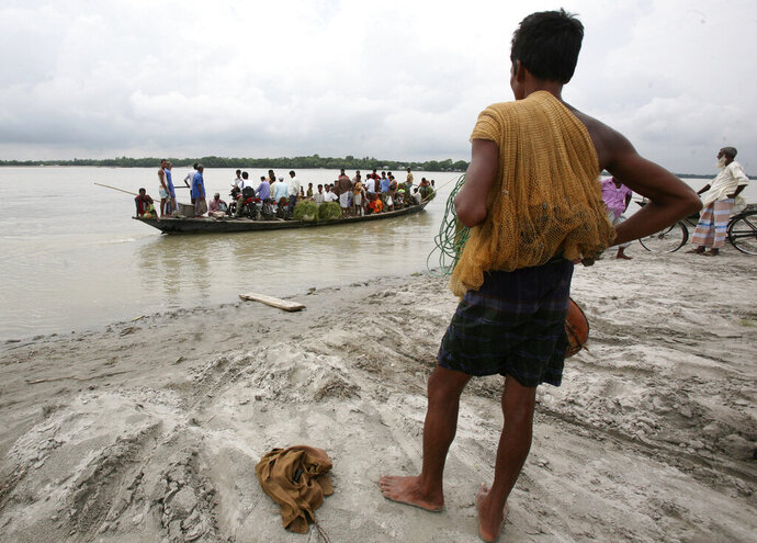 FILE- In this Sept. 24, 2009 file photo, fisherman Mohammad Ali stands as a ferry crosses the River Jamuna in Sirajganj district, 104 kilometers (65 miles) northwest of capital Dhaka, Bangladesh. With the monsoon setting in and waters from India rushing downstream, Bangladesh is facing a serious threat of floods that could cause extensive damage to farmlands across the delta nation's vast northern regions, officials said Sunday, June 28, 2020. Abdur Rahim, a disaster management official in northern Sirajganj district, said about 50,000 families have already been affected after the Jamuna River swelled. (AP Photo/Pavel Rahman, File)