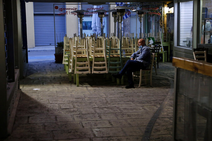 A man wearing a face mask sits by stacked chairs outside of a closed restaurant in central Nicosia, Cyprus, Thursday, Feb. 25, 2021. Cyprus will send all high school students back to their classrooms and open up gyms, pools, dance academies and art galleries next week in a further, incremental easing of the country's second nationwide COVID-19 lockdown. (AP Photo/Petros Karadjias)