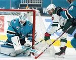 San Jose Sharks goaltender Martin Jones (31) blocks a goal attempt by Minnesota Wild left wing Jordan Greenway (18) during the second period of an NHL hockey game in San Jose, Calif., Monday, Feb. 22, 2021. (AP Photo/Tony Avelar)