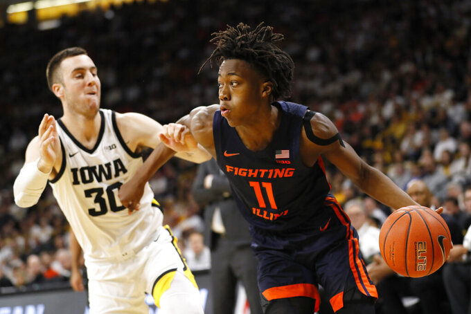 FILE - In this Feb. 2, 2020, file photo, Illinois guard Ayo Dosunmu drives to the basket past Iowa guard Connor McCaffery, left, during the first half of an NCAA college basketball game in Iowa City, Iowa. Dosunmu was selected to the Associated Press All-Big Ten team selected Tuesday, March 10, 2020.(AP Photo/Charlie Neibergall, File)
