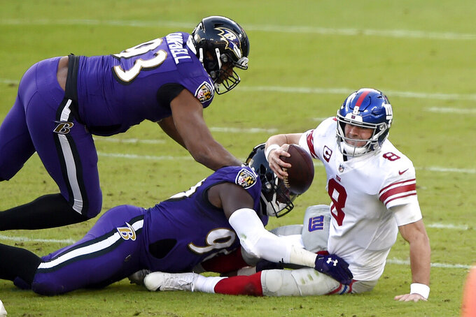 New York Giants quarterback Daniel Jones (8) is sacked by Baltimore Ravens outside linebacker Pernell McPhee (90) during the second half of an NFL football game, Sunday, Dec. 27, 2020, in Baltimore. Ravens Calais Campbell (93) helps on the play. (AP Photo/Gail Burton)