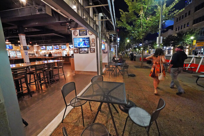 FILE - In this Sept, 9, 2020, file photo, a couple walk past Mike's Beer Bar, across the street from PNC Park, after a baseball game between the Chicago White Sox and Pittsburgh Pirates in Pittsburgh. Small businesses around PNC Park and other downtown stadiums across Major League Baseball are struggling due to the COVID-19 pandemic, which forced MLB to ban fans from attending games during the truncated 2020 seasons. (AP Photo/Gene J. Puskar, File)