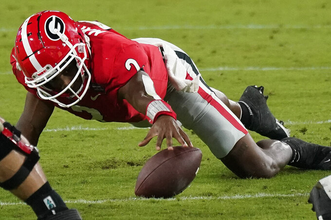 Georgia quarterback D'Wan Mathis (2) recovers his own fumble during the second half of an NCAA college football game against Florida, Saturday, Nov. 7, 2020, in Jacksonville, Fla. (AP Photo/John Raoux)