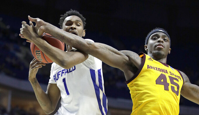 Buffalo's Montell McRae (1) and Arizona State's Zylan Cheatham (45) battle for a rebound during the first half of a first round men's college basketball game in the NCAA Tournament Friday, March 22, 2019, in Tulsa, Okla. (AP Photo/Charlie Riedel)