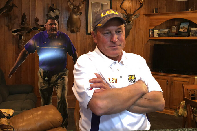 """Don """"Noochie"""" Adams stands in front of a cardboard cutout of childhood friend Ed Orgeron, the NCAA college football coach at LSU, in his home in Cut Off, La., Thursday, Jan. 9, 2020. Cajun pride is swelling in Lafourche Parish now that the former two-way football standout who won a 1977 state title for the South Lafourche High School Tarpons is on the brink of capping off arguably the LSU Tigers' greatest season in the program's 126-year history with a national title. No. 1 LSU plays third-ranked Clemson on Monday night in the College Football Playoff championship in New Orleans, about 60 miles northeast of where Orgeron grew up. (AP Photo/Brett Martel)"""