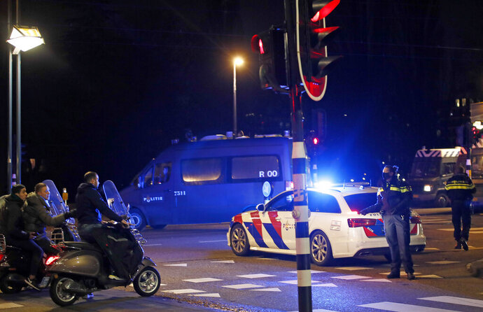 A police officers speaks to youths on scooters at a road block during a nation-wide curfew in Amsterdam, Netherlands, Tuesday, Jan. 26, 2021. The Netherlands entered its toughest phase of anti-coronavirus restrictions to date, imposing a nationwide night-time curfew from 9 p.m. until 4:30 a.m. which started Saturday Jan. 23, 2021, in a bid to control the COVID-19 infection rate. (AP Photo/Peter Dejong)