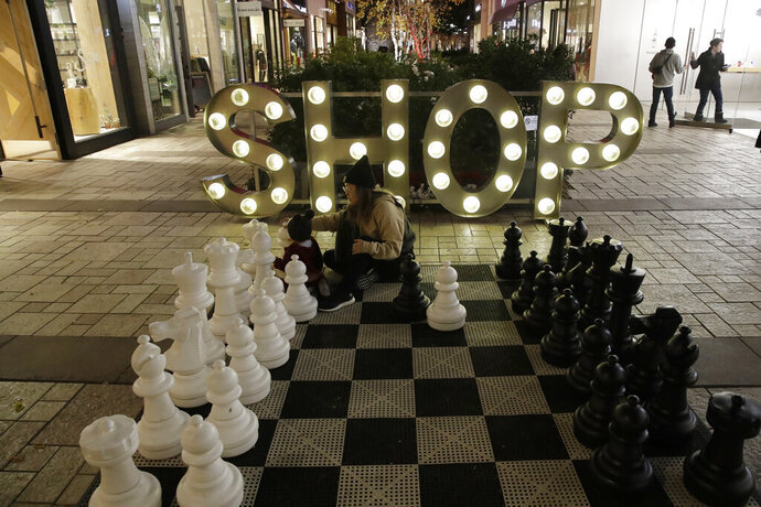 FILE - In this Dec. 16, 2019, file photo a shopping district is decorated for the holidays in Santa Clarita, Calif. On Tuesday, Dec. 31, the Conference Board reports on U.S. consumer confidence for December. (AP Photo/Marcio Jose Sanchez, File)