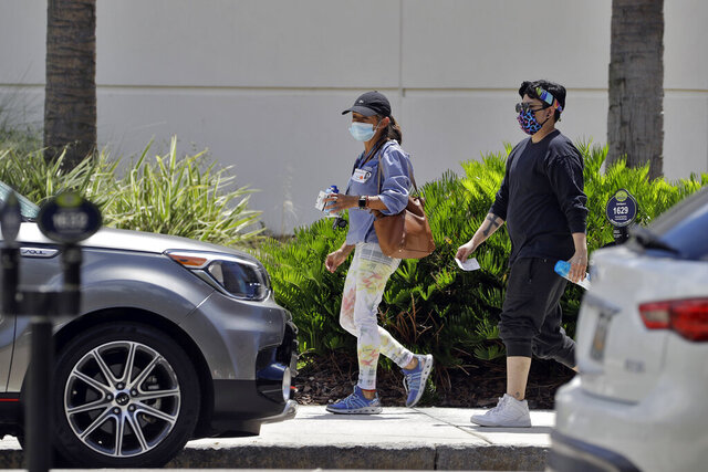 Two women wear protective masks as they walk outside a county office building Tuesday, June 23, 2020, in Tampa, Fla. Members of the Hillsborough County Emergency Policy Group voted 5-3 on Monday to implement an executive order that would require the wearing of protective face coverings throughout Hillsborough County. The executive order requires everyone inside a for-profit business that is open to the public to wear a mask when social distancing cannot be maintained, excluding family members or others residing in your home. (AP Photo/Chris O'Meara)
