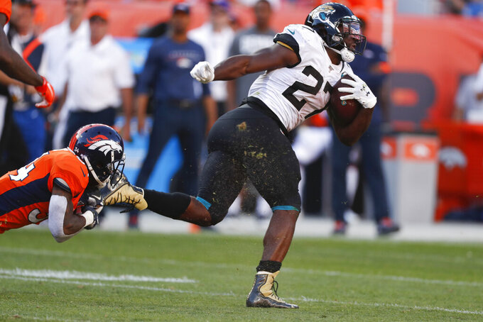 Jacksonville Jaguars running back Leonard Fournette, right, runs with the ball during the second half of an NFL football game against the Denver Broncos, Sunday, Sept. 29, 2019, in Denver. (AP Photo/David Zalubowski)