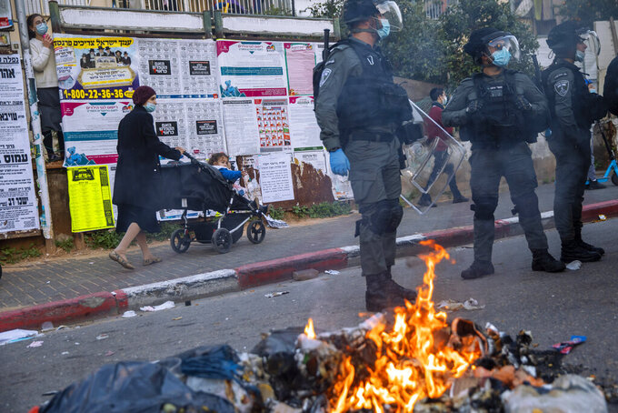 Israeli police officers stand by burning garbage during clashes with ultra-Orthodox Jews over the coronavirus lockdown restrictions, in Bnei Brak, Israel, Sunday, Jan. 24, 2021. As he seeks re-election, Prime Minister Benjamin Netanyahu has turned to a straightforward strategy: Count on the rock-solid support of his ultra-Orthodox political allies and stamp out the coronavirus pandemic with one of the world's most aggressive vaccination campaigns. But with ultra-Orthodox communities openly flouting safety guidelines and violently clashing with police trying to enforce them, this marriage of convenience is turning into a burden. (AP Photo/Oded Balilty)