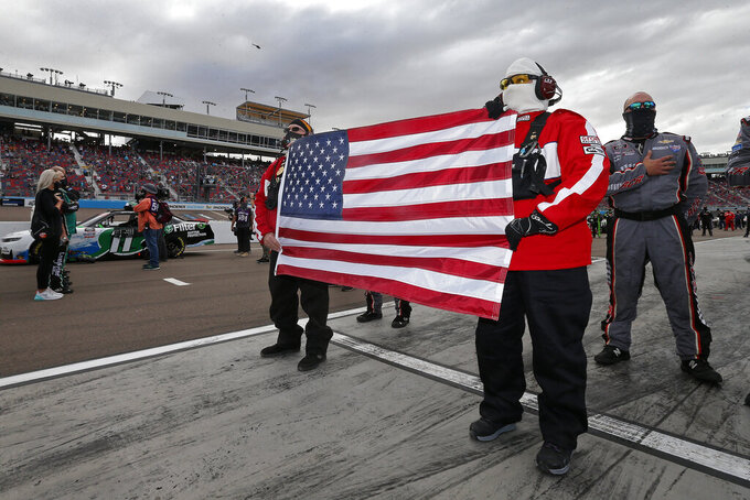 Fire and Safety crew members hold a United States flag on pit road prior to an NASCAR Xfinity Series auto race at Phoenix Raceway, Saturday, Nov. 7, 2020, in Avondale, Ariz. (AP Photo/Ralph Freso)
