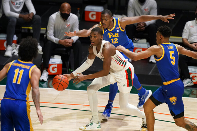 Miami forward Anthony Walker, center, looks for an opening past Pittsburgh forwards Justin Champagnie (11) Abdoul Karim Coulibaly (12) and guard Au'diese Toney (5) during the second half of an NCAA college basketball game, Wednesday, Dec. 16, 2020, in Coral Gables, Fla. (AP Photo/Wilfredo Lee)