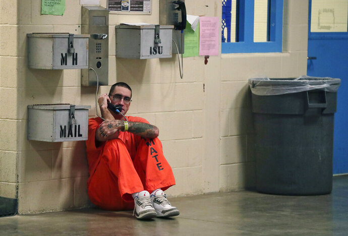 FILE - In this Nov. 27, 2017 file photo, inmate Lance Shaver talks on the phone at the Albany County Correctional Facility in Albany, N.Y. Connecticut is considering legislation which would make phone calls from prison free to inmates. (AP Photo/Julie Jacobson, File)