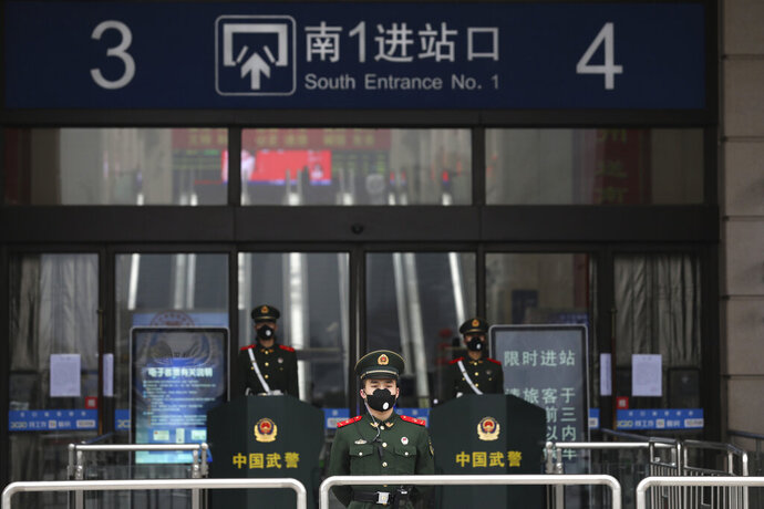 FILE - In this Jan. 23, 2020, file photo, Chinese paramilitary police stand guard outside the closed Hankou Railway Station in Wuhan in central China's Hubei Province. Cutting off access to entire cities with millions of residents to stop a new virus outbreak is a step few countries other than China would consider, but it is made possible by the ruling Communist Party's extensive social controls and experience fighting the 2002-03 outbreak of SARS. (Chinatopix via AP, File)