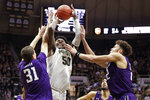 Purdue forward Trevion Williams (50) shoots between Northwestern forward Robbie Beran (31) and forward Pete Nance (22) during the second half of an NCAA college basketball game in West Lafayette, Ind., Sunday, Dec. 8, 2019. Purdue defeated Northwestern 58-44. (AP Photo/Michael Conroy)