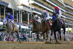John Velazquez riding Medina Spirit, right, leads Florent Geroux on Mandaloun, Flavien Prat riding Hot Rod Charlie and Luis Saez on Essential Quality to win the 147th running of the Kentucky Derby at Churchill Downs, Saturday, May 1, 2021, in Louisville, Ky. (AP Photo/Jeff Roberson)