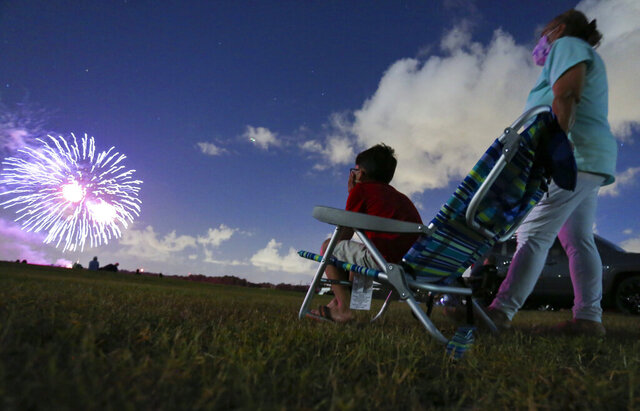Javonnie Jackson, 9, left, sits with his grandmother Zoraida Rullan, 69, watching fireworks explode over Nathan Benderson Park on Friday, July 3, 2020, in Sarasota, Fl. The pair were reunited after nearly five months of separation due to the coronavirus. (Jonah Hinebaugh/Tampa Bay Times via AP)
