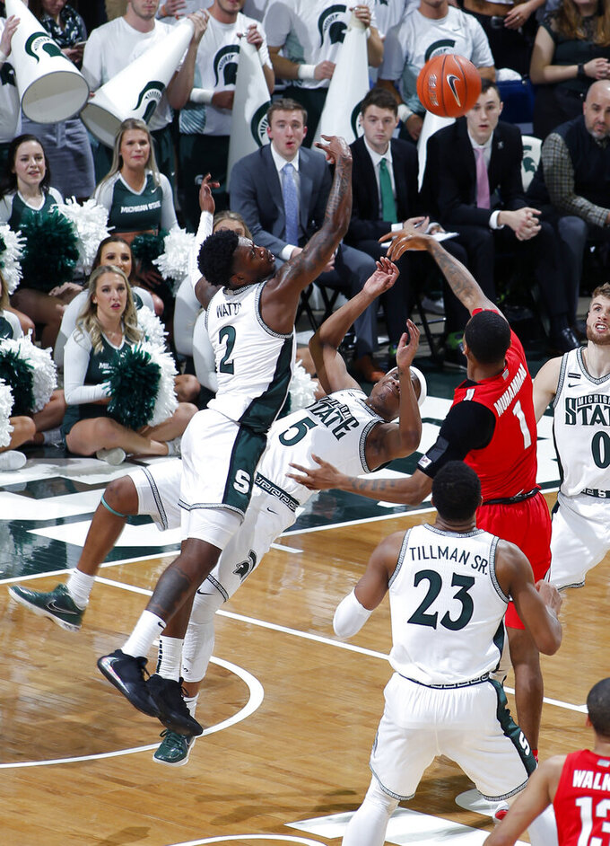 Michigan State's Rocket Watts, left, and Cassius Winston (5) and Ohio State's Luther Muhammad (1) battle for a rebound during the first half of an NCAA college basketball game, Sunday, March 8, 2020, in East Lansing, Mich. (AP Photo/Al Goldis)