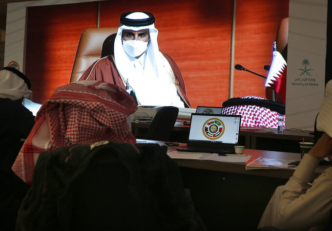 Saudi journalists watch a large display screen in a media center, showing Qatar's Emir Sheikh Tamim bin Hamad Al Thani, at the 41st Gulf Cooperation Council (GCC) meeting, in Al Ula, Saudi Arabia, Tuesday, Jan. 5, 2021. Qatar's ruling emir arrived in Saudi Arabia to attend the high-level summit of Arab leaders, following an announcement that the kingdom would end its yearslong embargo on the tiny Gulf state. The Qatari emir's arrival in the kingdom's ancient desert city of Al-Ula on Tuesday was broadcast live on Saudi TV. (AP Photo/Amr Nabil)