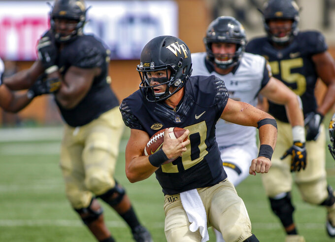 FILE - In this Saturday, Sept. 8, 2018, file photo, Wake Forest quarterback Sam Hartman carries the ball against Towson in the second half of an NCAA college football game in Winston-Salem, N.C. Hartman won the job in camp after presumptive starter Kendall Hinton was suspended for three games for violating team rules. The former backup is second in the ACC with 278 passing yards per game to go with six touchdowns and five interceptions (AP Photo/Nell Redmond, File)