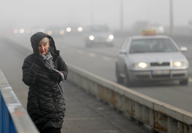 A woman walks across a busy bridge in Belgrade, Serbia, Wednesday, Jan. 15, 2020. Serbia's government on Wednesday called an emergency meeting, as many cities throughout the Balkans have been hit by dangerous levels of air pollution in recent days, prompting residents' anger and government warnings to stay indoors and avoid physical activity. (AP Photo/Darko Vojinovic)
