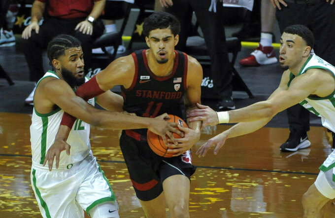 Oregon guard LJ Figueroa (12) and Oregon guard Chris Duarte (5) try to steal the ball from Stanford forward Jaiden Delaire (11) during the first half of an NCAA college basketball game Saturday, Jan. 2, 2021, in Eugene, Ore. (AP Photo/Andy Nelson)