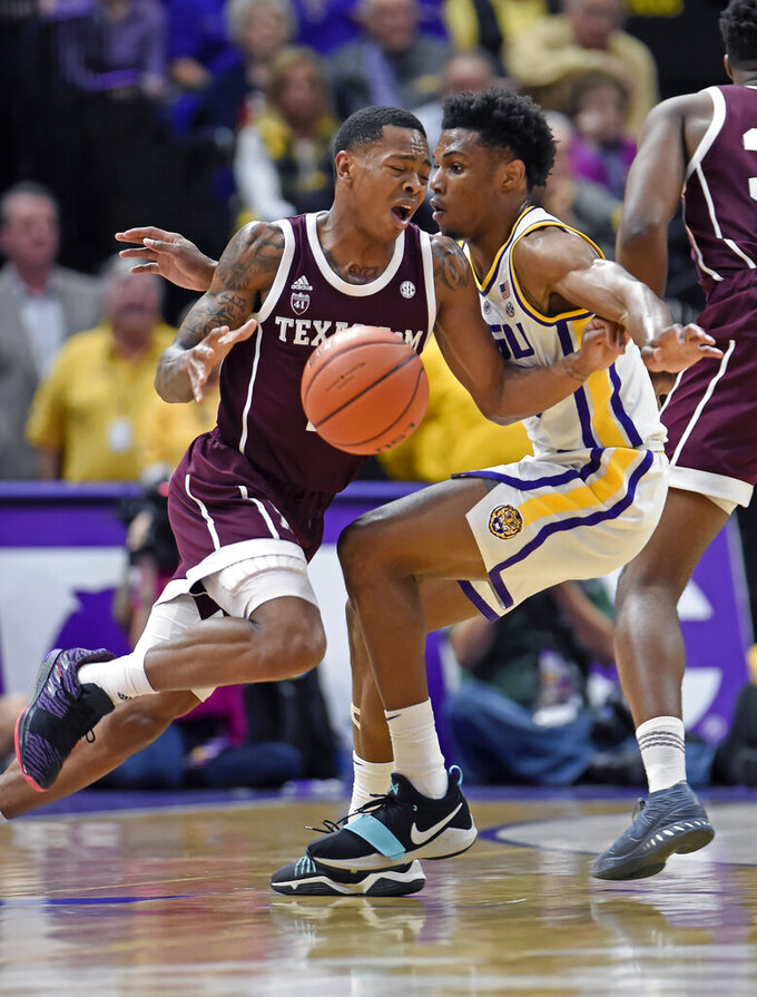 Texas A&M guard Wendell Mitchell, left, and LSU guard Marlon Taylor (14) collide in the first half of an NCAA college basketball game, Tuesday, Feb. 26, 2019, in Baton Rouge, La. (AP Photo/Bill Feig)
