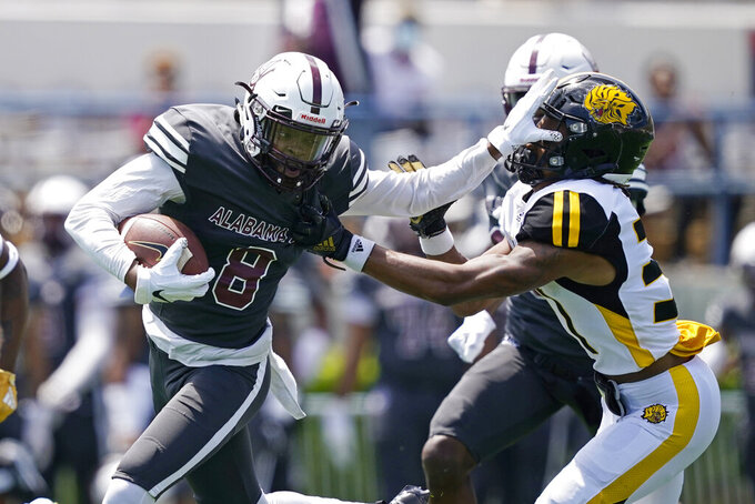 Alabama A&M wide receiver Zabrian Moore (8) attempts to fight off a tackle by an Arkansas-Pine Bluff defender after a pass reception during the first half of the Southwestern Athletic Conference NCAA college football game, Saturday, May 1, 2021, in Jackson, Miss. (AP Photo/Rogelio V. Solis)
