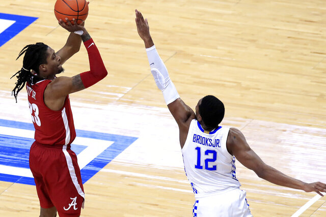 Alabama's John Petty Jr., left, shoots a 3-pointer while defended by Kentucky's Keion Brooks Jr. (12) during the first half of an NCAA college basketball game in Lexington, Ky., Tuesday, Jan. 12, 2021. (AP Photo/James Crisp)
