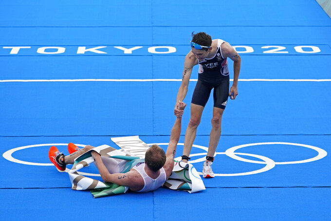 Alex Yee of Great Britain (55) reaches to help up Kristian Blummenfelt of Team Norway (43) after Blummenfelt won the gold medal and Yee won silver during the men's individual triathlon at the 2020 Summer Olympics, Monday, July 26, 2021, in Tokyo, Japan. (AP Photo/David Goldman)