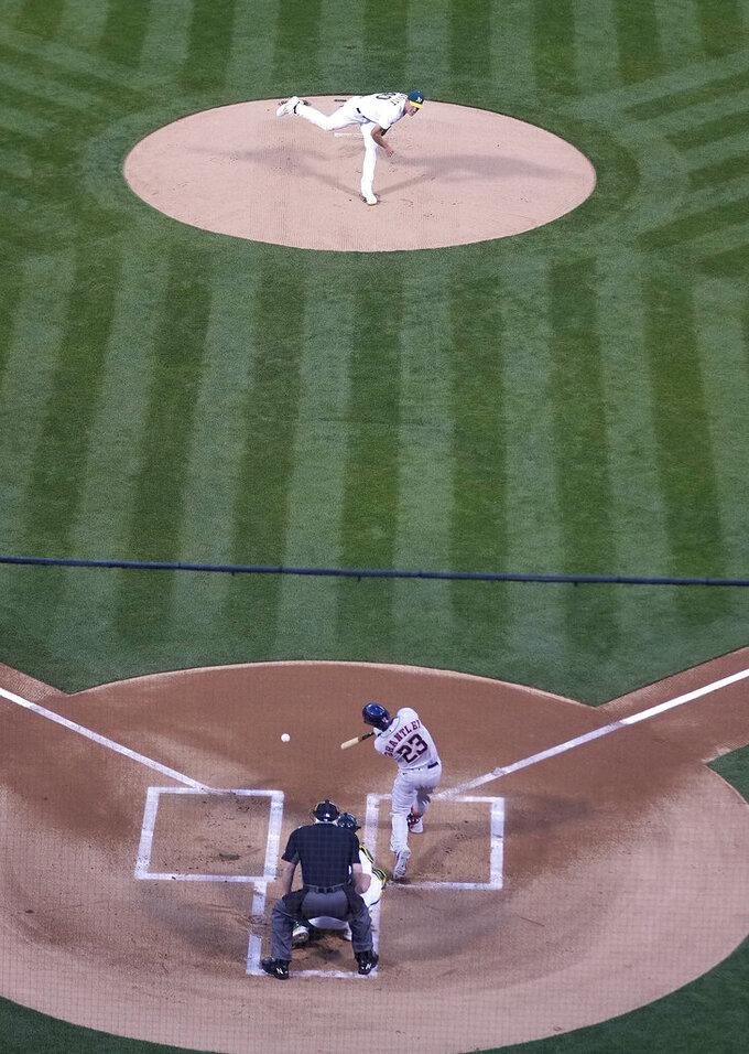 Oakland Athletics pitcher Chris Bassitt (40) works against the Houston Astros' Michael Brantley (23) in the first inning of an opening day baseball game Oakland, Calif., Thursday, April 1, 2021. (AP Photo/Tony Avelar)