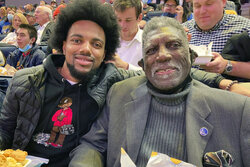 Golden State Warriors Hall of Famer Al Attles, right, sits with his grandson and Lincoln basketball player Isaiah Attles, at an NBA basketball game between the Warriors and the Los Angeles Clippers, Thursday, Oct. 21, 2021, in San Francisco. Hall of Famer Gary Payton is the new men's basketball coach at Lincoln University, determined to make a lasting mark in his hometown of Oakland, Calif. (AP Photo/Janie McCauley)