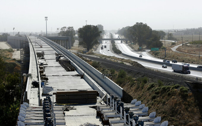 FILE - This Oct. 9, 2019, file photo shows the high speed rail viaduct paralleling Highway 99 near Fresno, Calif. Brian Kelly, the chief executive officer of The California High-Speed Rail Authority, said in a letter released Friday, Feb. 5, 2021, that a 119-mile segment of track in the Central Valley now won't be completed until 2023, a one-year delay. (AP Photo/Rich Pedroncelli, File)