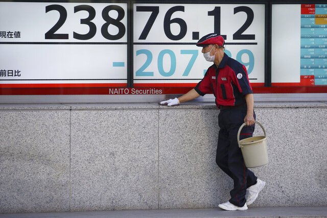 A worker cleans up an electronic stock board of a securities firm in Tokyo, Tuesday, Jan. 21, 2020. Asian stock markets have tumbled as concern about the impact of a Chinese disease outbreak on tourism and regional economies grows. (AP Photo/Koji Sasahara)