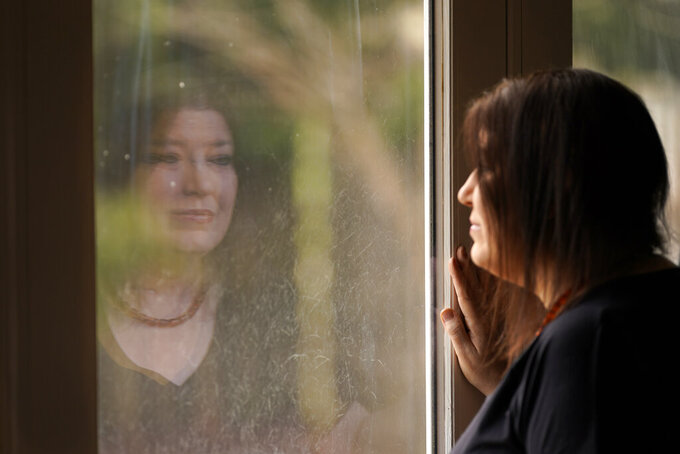 CORRECTS TO KARI, NOT KERI - Kari Wegg is reflected in a sliding glass door as she looks outside her home in Westfield, Ind., on Monday, March 22, 2021. The Indiana nurse came down with COVID-19 in the summer of 2020; her condition spiraled downward, and her life was saved only by grace of a double lung transplant. The road to normal is a long one, but she's bolstered by the love and support of her husband and sons, and by her own indomitable spirit. (AP Photo/Charles Rex Arbogast)