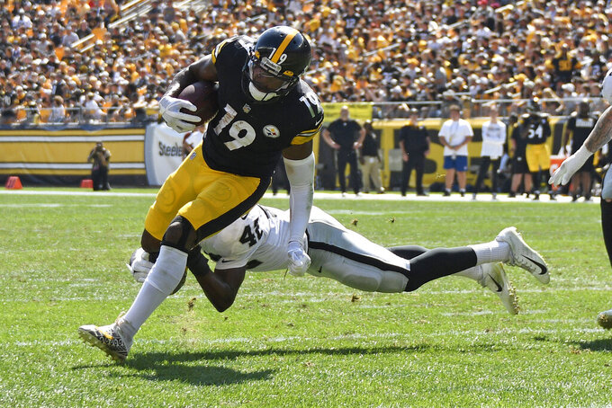 Pittsburgh Steelers wide receiver JuJu Smith-Schuster (19) gets past Las Vegas Raiders inside linebacker Cory Littleton (42) for a touchdown during the first half of an NFL football game in Pittsburgh, Sunday, Sept. 19, 2021. (AP Photo/Don Wright)