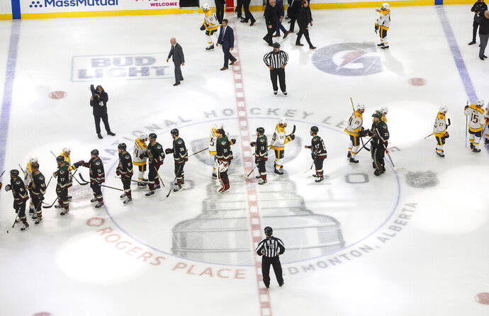 Nashville Predators and the Arizona Coyotes shake hands following overtime in an NHL hockey playoff game Friday, Aug. 7, 2020, in Edmonton, Alberta. (Jason Franson/Canadian Press via AP)
