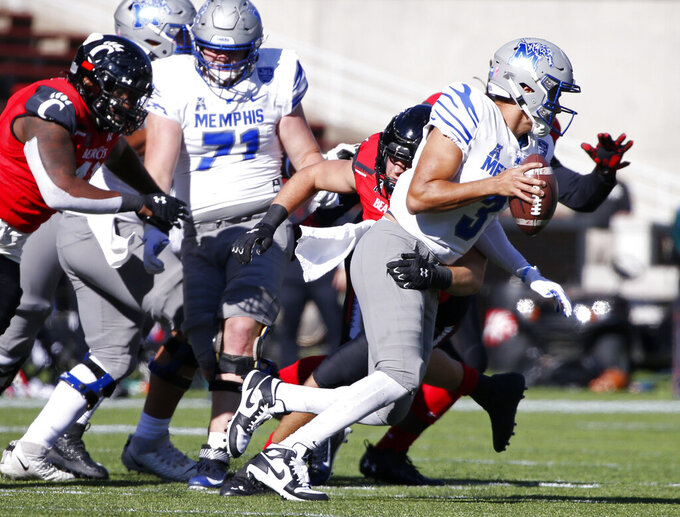 Memphis quarterback Brady White (3) scrambles from the pocket as he is pursued by Cincinnati linebacker Wilson Huber, rear, during the second half of an NCAA college football game Saturday, Oct. 31, 2020, in Cincinnati. Cincinnati won 49-10. (Photo by Gary Landers)