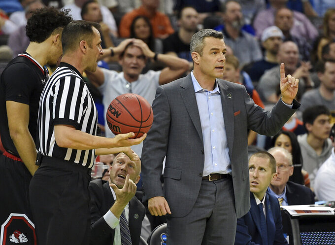 Virginia head coach Tony Bennett, right, speaks to an official during a first-round game against Gardner-Webb in the NCAA men's college basketball tournament in Columbia, S.C. Friday, March 22, 2019. (AP Photo/Richard Shiro)